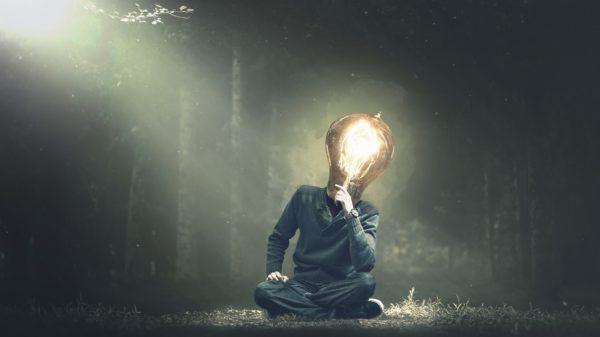 Homme tête d'ampoule seul en forêt