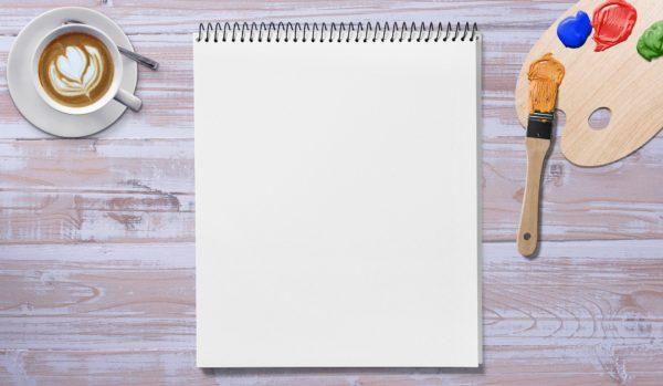 Bureau avec carnet et palette de peinture ainsi qu'une tasse de café